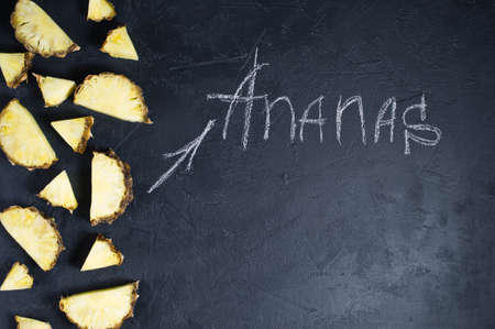 Pineapple slices on black background with space for text and chalk inscription