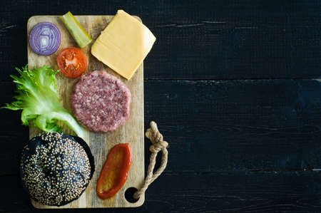 Ingredients for black Burger on wooden chopping Board, black background Banque d'images - 121635798