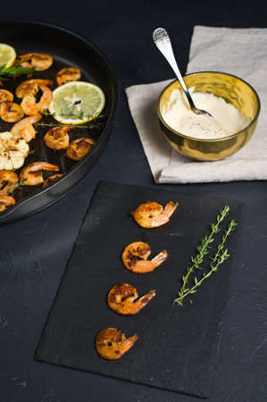 Fried king prawns in a frying pan on a black background with a bowl of sauce