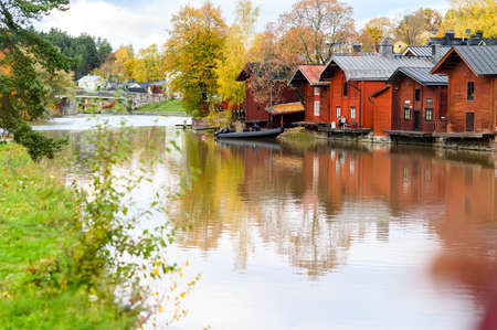 The granite embankment with red houses and barns. Beautiful autumn landscape. Historic centre. Porvoo, Finland.