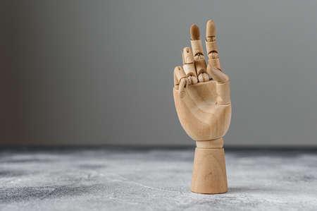 La mano de madera muestra dos dedos levantados. El concepto de comunicación