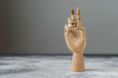 The wooden hand shows two raised fingers. The concept of communication Foto de archivo