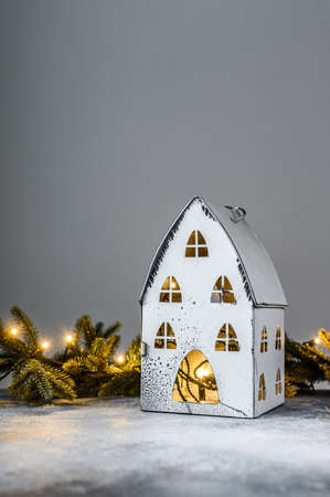 Christmas background, candlestick house with lights, fir branches and Christmas toys. Happy new year
