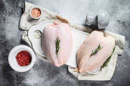 Raw chicken Breasts, fresh fillets with skin. Organic farm bird. Gray background.