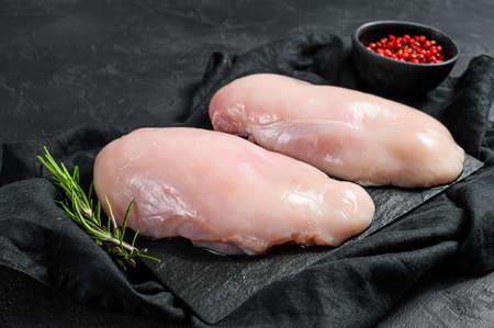 Raw chicken fillet on a cutting Board. Fresh Breasts. Black background. Farm organic meat
