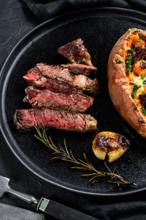 Rib eye steak garnished with baked sweet potato. Grilled beef. Organic farm meat. Black background.