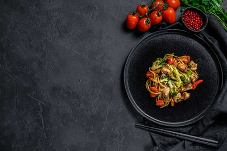 Stir fry noodles, traditional Chinese wok. chopsticks, ingredients. Space for text. Asian noodles with vegetables, meat. Black dark background. Top view.