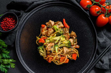 Chicken stir fry with vegetables soy sause, wok. Traditional asian food. stone black table.