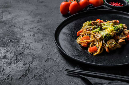 Soba noodles with beef, carrots, onions and sweet peppers. Top view. Dark background. Space for text. 写真素材