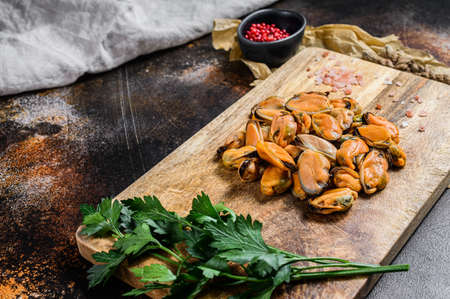 Carne de mejillón cruda fresca sobre una tabla de cortar de madera. Mariscos saludables. Foto de archivo