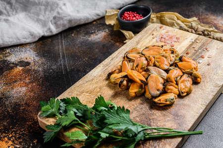 Carne di cozze cruda fresca su un tagliere di legno. Frutti di mare sani. Archivio Fotografico