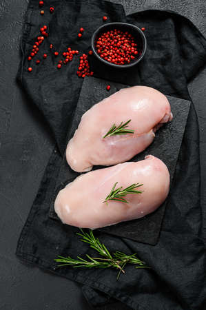 Raw chicken Breasts on a chopping Board. Fresh fillet. Black background. Space for text.