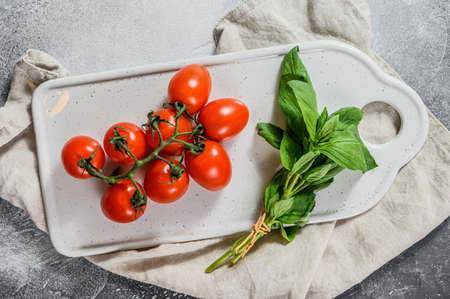 Fresh cherry tomatoes on a white background with basil. Top view