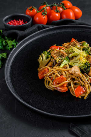 Stir fry noodles, traditional Chinese wok. chopsticks, ingredients. Asian noodles with vegetables, meat. Black dark background. Top view