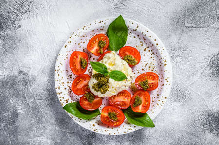 Italian cheese stracciatella (burrata) on small plate served with fresh tomatoes and basil. Gray background. Space for text Zdjęcie Seryjne