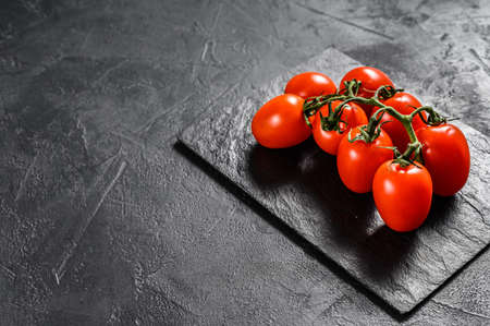 Red cherry tomatoes on a black background. Space for text