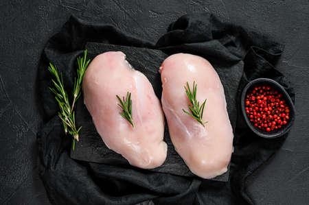 Organic farm meat. Raw chicken Breasts on a chopping Board. Fresh fillet. Black background.