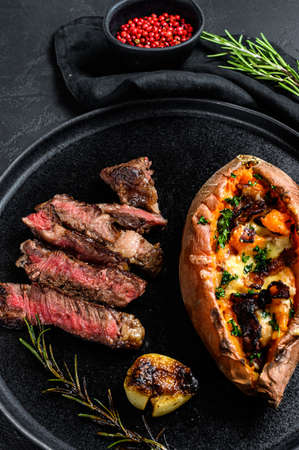 Marbled beef steak with baked sweet potato garnish. Grilled meat. Organic farm meat. Black background. Stock Photo