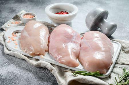 Raw Turkey Breasts on a white chopping Board. Organic farm bird. Fresh fillet. Gray background.