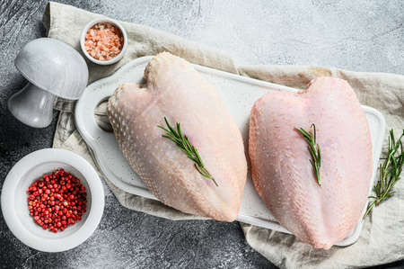 Raw chicken Breasts on a white chopping Board. Organic farm bird. Fresh fillet with skin. Gray background.