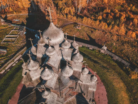 Aerial view of the Old wooden Church Manor Theologian in the autumn forest. Russia, St. Petersburg