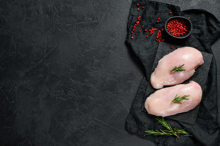 Organic farm meat. Raw chicken Breasts on a chopping Board. Fresh fillet. Black background. Space for text.