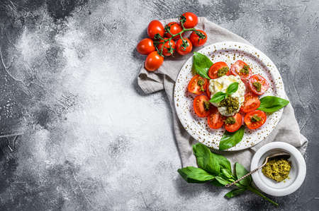 Italian cheese stracciatella (burrata) on small plate served with fresh tomatoes and basil. Gray background. Space for text.