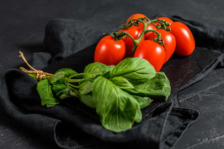 tomatoes on a BLACK background with basil. Top view