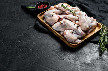 Raw chicken wings. Farm organic poultry. Top view. Black background. Space for text