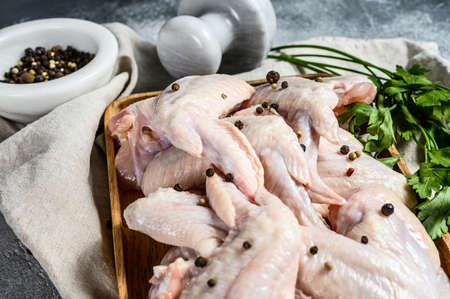 Raw chicken wings in a wooden bowl. Top view. Gray background. Stok Fotoğraf