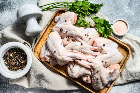 Raw chicken wings. Farm organic poultry. Top view. Gray background. Stok Fotoğraf