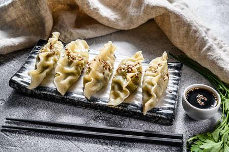 Steam Korean dumplings on a ceramic plate. Gray background. Top view.