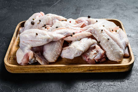 Raw chicken wings. Farm organic poultry. Top view. Black background