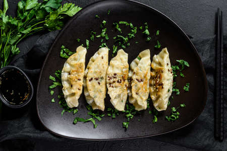 Pork Potstickers on rustic black table. Dim sum on a plate. Top view Stock Photo