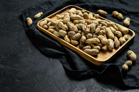 Raw unshelled peanuts in the shell. Organic groundnut. Black background. The view from the top. Space for text.