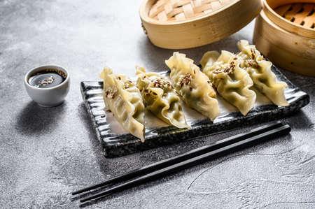 Korean dumplings on a ceramic plate. Black chopsticks and a bamboo steamer. Gray background. Top view