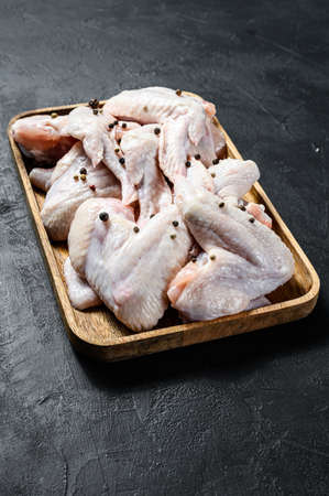 Raw chicken wings in a wooden bowl. Farm organic meat. Top view. Black background.
