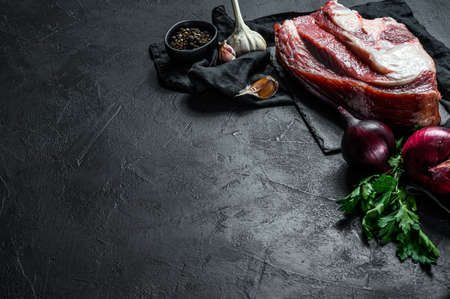 Raw beef shank on black background. Top view. Space for text