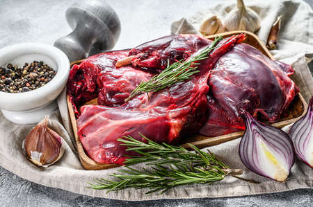 Rabbit meat. Raw fresh farm rabbit on a wooden table with vegetables and spices. Top view. Organic meat.