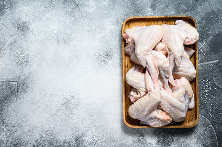 Raw chicken wings in a wooden bowl. Top view. Gray background. Space for text. Stok Fotoğraf