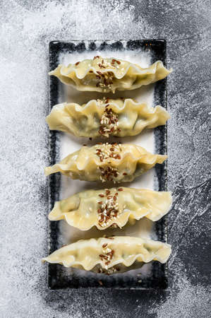 Steam Japanese gyoza on a ceramic plate. Gray background. Top view.