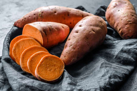 Raw sweet potatoes, organic yam. The farm food. Black background.