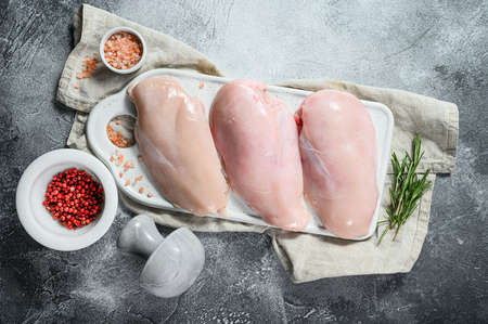 Organic farm meat. Raw chicken Breasts on a white chopping Board. Fresh fillet. Gray background.