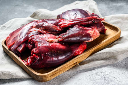 Hare meat. Raw fresh wild hare on a wooden table with vegetables and spices. Top view. Organic meat.