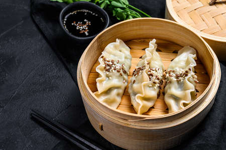 Japanese gyoza in a traditional bamboo steamer. Top view. Space for text. rustic old vintage black background. Stock Photo