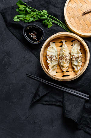 Korean dumplings in a traditional bamboo steamer. Top view. Space for text. rustic old vintage black background.