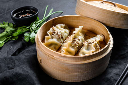 Japanese gyoza in a traditional bamboo steamer. Top view. Rustic old vintage black background.