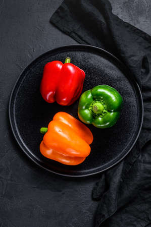 Green, orange and red bell peppers on a plate. Black background. Top view. Imagens