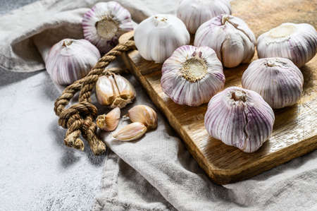 Garlic Bulb and garlic cloves on a wooden cutting Board. Organic farm food. Gray background. Top view. Close up.