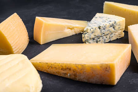 Different types of delicious cheese. Black background. Top view Archivio Fotografico